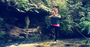 gopika-yoga-in-schwäbisch-hall - das Bild zeigt Michaela Langer in der Yogaposition Baum in Naturlandschaft mit einem Fluß und Heiligenfigur