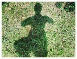 gopika-yoga-in-schwäbisch-hall - das Bild zeigt den Schatten von Michaela Langer auf einer grünen Wiese in der Yogaposition Baum