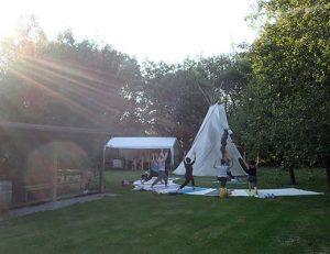 gopika-yoga-in-schwäbisch-hall_outdoor-yoga - das Bild zeigt eine Gruppe von Yogaübenden im Freien vor einem Tipi Zelt