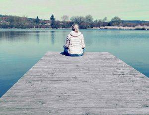 gopika-yoga-in-schwäbisch-hall - das Bild zeigt Michaela Langer auf einem Seesteg sitzend.
