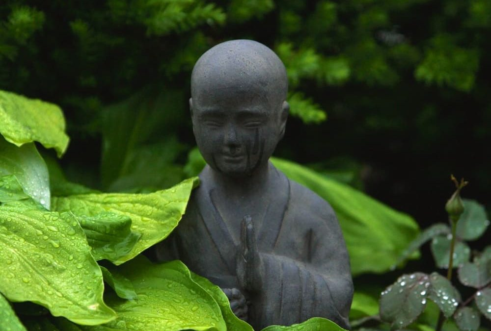 gopika-yoga-in-schwäbisch-hall-das bild zeigt eine steinerne Buddhastatue, die in einm Garten steht und teilweise von regennassen Blättern bedeckt ist.