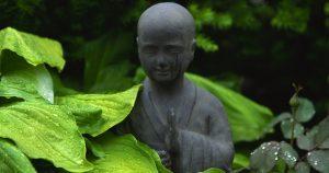 gopika-yoga-in-schwäbisch-hall-das bild zeigt eine steinerne Buddhastatue, die in einm Garten steht und teilweise von Blättern bedeckt ist.