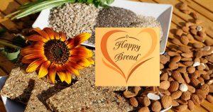 gopika-yoga-in-schwaebisch-hall - auf dem Bild sieht man einen schön dekorierten Teller mit Brotscheiben, verschiedenen Körnern, Mandeln, einer Sonnenblume und dem Logo von Happy Bread
