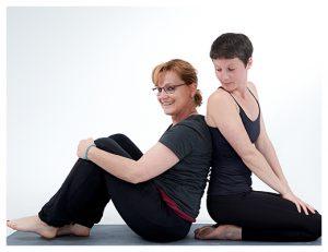 gopika-yoga-in-schwäbisch-hall - auf dem bild sitzt Michaela Langer mit einer Freundin Rücken an Rücken auf einer Yogamatte