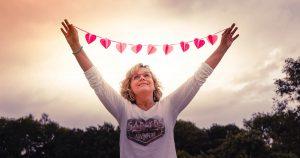 gopika-yoga-in-schwäbisch-hall - auf dem Bild hält michaela langer eine rosafarbene girlande mit herzen zwischen den ausgestreckten armen