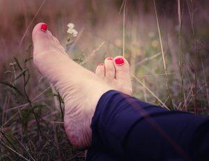 gopika-yoga-in-schwäbisch-hall - das bild zeigt zwei gekreuzte füße mit rot lackierten fußnägeln