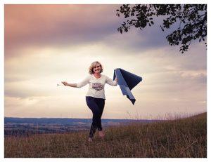 gopika-yoga-in-schwäbisch-hall - auf dem foto sieht man michaela langer mit einer yogamatte in der hand über eine wiese laufen