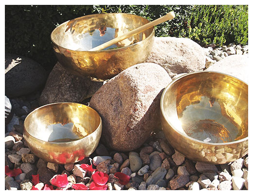 gopika-yoga-in-schwäbisch-hall - das bild zeigt drei goldfarbene klangschalen, die zwischen steinen stehen