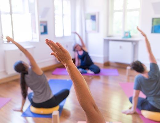 gopika-yoga-in-schwäbisch-hall - wir sehen eine übernde yogagruppe in einer dehnung