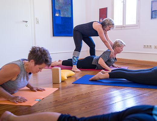 gopika-yoga-in-schwäbisch-hall - man sieht michaela langer bei der korrektur ihrer kursteilnehmer während einer yogaübung