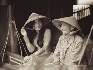 Das Bild zeigt eine junge Frau und eine ältere Frau, die zusammen sitzen und lächeln